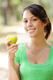 Young woman with green apple. Portrait of young woman with green apple, smiling and looking in camera Stock Images