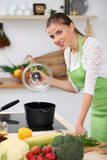 Young woman in the green apron cooking in the kitchen. Housewife is preparing the soup. Stock Photo