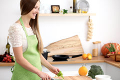 Young woman in the green apron cooking in the kitchen. Housewife slicing fresh salad.  Royalty Free Stock Images
