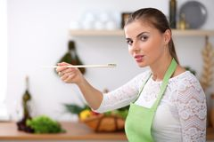 Young woman in green apron is cooking in a kitchen. Housewife is tasting fresh salad by wooden spoon. Young woman in green apron is cooking in a kitchen Stock Image