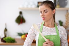 Young woman in the green apron is cooking in the kitchen. Housewife thinking about the menu while holding a wooden spoon Royalty Free Stock Image