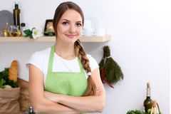 Young woman in green apron is going for cooking in a kitchen. Housewife is tasting the soup by wooden spoon. Young woman in green apron is going for cooking in Stock Image