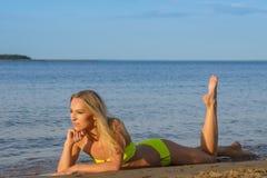 Young woman in green bikini posing on a beach Royalty Free Stock Photography