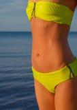 Young woman in green bikini posing on a beach Stock Image