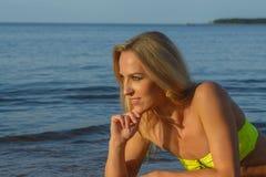 Young woman in green bikini posing on a beach Stock Photography
