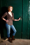 Young woman by a green door Royalty Free Stock Photo