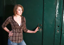 A young woman by a green door Royalty Free Stock Photos