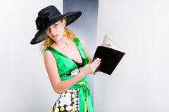 Young Woman in a green dress and black hat Stock Images