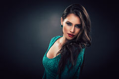 Young woman in a green dress with curly long hair Royalty Free Stock Image