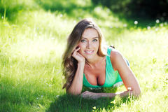 Young woman in green dress lying on grass Royalty Free Stock Image