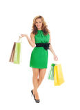 A young woman in a green dress with shopping bags Stock Photography
