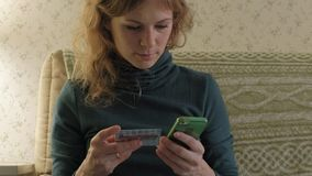 A young woman in a green dress sits on a sofa with a laptop, uses a telephone and a plastic card, works, studies. Documents, work at home, business 4k stock footage