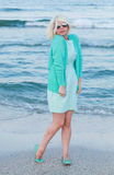 Young woman in green dress and sunglasses on seashore. Woman in green dress and sea. Royalty Free Stock Images