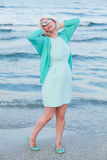 Young woman in green dress and sunglasses on seashore. Woman in green dress and sea. Royalty Free Stock Image