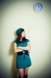 Young woman in green dress waiting and looking up at wall clock Stock Photo