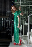 Young woman in green fashion dress walk on stairs Stock Image