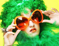Young woman with green hair and carnaval glasses. Happy young woman with green hair and carnaval glasses royalty free stock images