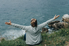 Young woman in a green jacket raise hand and  looks at the sea f Royalty Free Stock Photos