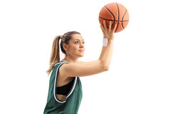 Young woman in a green jersey throwing a basketball Stock Photography