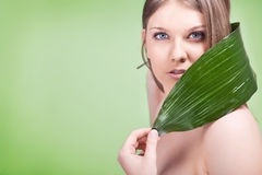 Young woman with green leaf Stock Images
