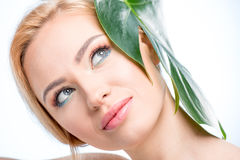 Young woman with green leaf on head smiling and looking up, skincare concept Stock Photos