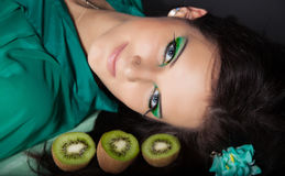 Young woman with green makeup. Young woman lying among kiwi with multicolored make up and looking at you Royalty Free Stock Photos