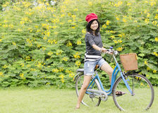 Young woman on a green meadow with a bicycle Royalty Free Stock Photos
