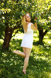 Young woman in a green orchard, smiling playfully Royalty Free Stock Photos