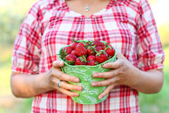 Young woman with a green pail of strawberries outdoors Royalty Free Stock Photo