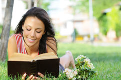 Young woman in green park, book and reading. Free time of young woman in green park, reading book Stock Photo