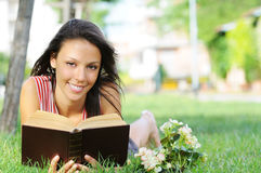 Young woman in green park, book and reading. Free time of young woman in green park, reading book Royalty Free Stock Image