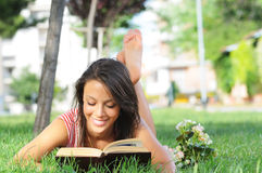 Young woman in green park, book and reading. Free time of young woman in green park, reading book Stock Photography