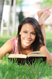 Young woman in green park, book and reading. Free time of young woman in green park, reading book Royalty Free Stock Photography