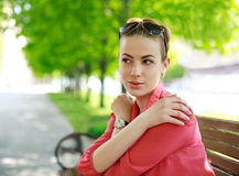 Young woman in green park, thoughtfully looking away Royalty Free Stock Photo