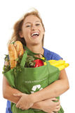 Young woman with green recycled grocery bag. Close-up of young woman with green recycled grocery bag of healthy food and vegetables Stock Image