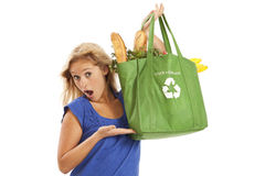 Young woman with green recycled grocery bag. Humorous portrait of young woman with green recycle bag Royalty Free Stock Image