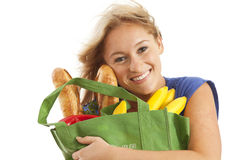 Young woman with green recycled grocery bag. Close-up of young woman with green recycled grocery bag of healthy food and vegetables Royalty Free Stock Photos