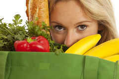 Young woman with green recycled grocery bag. Close-up of young woman with green recycled grocery bag of healthy food and vegetables Royalty Free Stock Photography