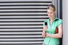Young woman in green short-sleeved blouse text messaging on mobile phone Stock Photos
