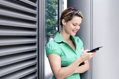 Young woman in green short-sleeved blouse text messaging on mobile phone, smiling, side view Stock Image