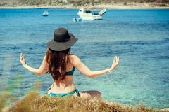 Young woman in green swimsuit and black hat practices yoga on the beach of the Mediterranean sea. qigong and freedom.  Royalty Free Stock Photography