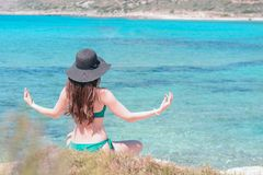 Young woman in green swimsuit and black hat practices yoga on the beach of the Mediterranean sea. qigong and freedom.  Stock Image