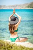 Young woman in green swimsuit and black hat practices yoga on the beach of the Mediterranean sea. qigong and freedom.  Stock Photography