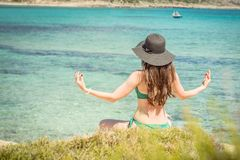 Young woman in green swimsuit and black hat practices yoga on the beach of the Mediterranean sea. qigong and freedom.  Royalty Free Stock Photos