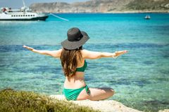 Young woman in green swimsuit and black hat practices yoga on the beach of the Mediterranean sea. qigong and freedom.  Stock Photo
