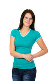 Young woman in green t-shirt and blue jeans posing over white Royalty Free Stock Image
