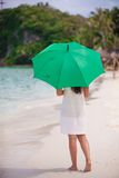 Young woman with green umbrella walking near the Royalty Free Stock Photography