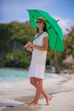 Young woman with green umbrella walking near the Royalty Free Stock Image
