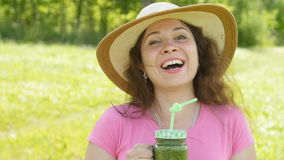 Young woman with green vegetable smoothies in the park stock footage