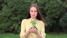 Young Woman with Green Young Plant In Hands stock video